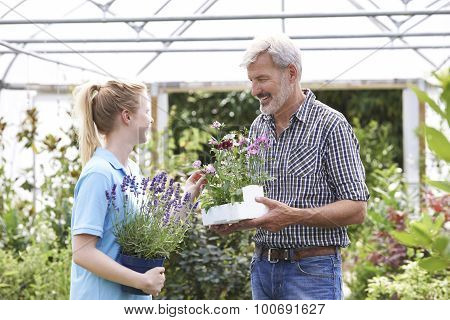 Male Customer Asking Staff For Plant Advice At Garden Center