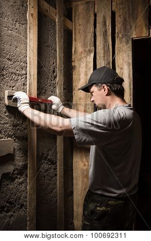 Builder Measures The Level Of The Wall