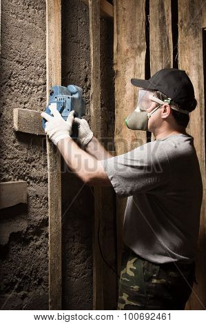 Builder In A Respirator And Goggles