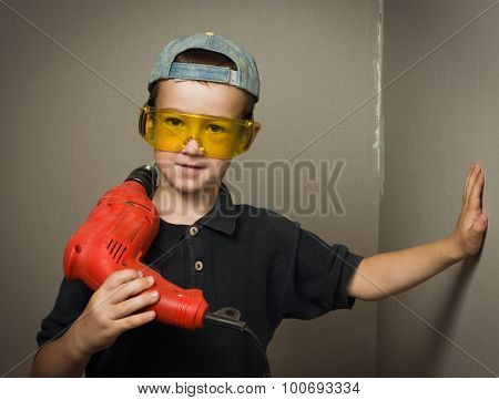 Boy In Goggles With Electric Drill