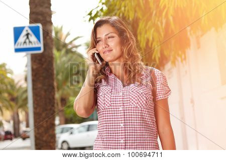 Young Lady Smiling While Speaking On Mobile Phone