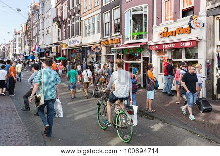 Tourists In Amsterdam Shopping And Looking For A Restaurant