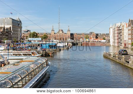 Canal With Landing Stage Of Cruise Ships Downtown In Amsterdam