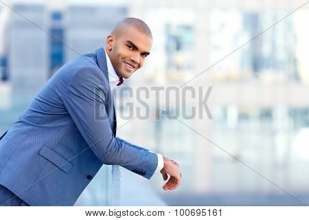 Happy businessman leaning on the handrail