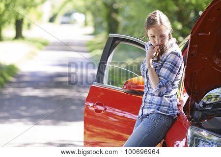 Worried Female Motorist Standing Next To Broken Down Car