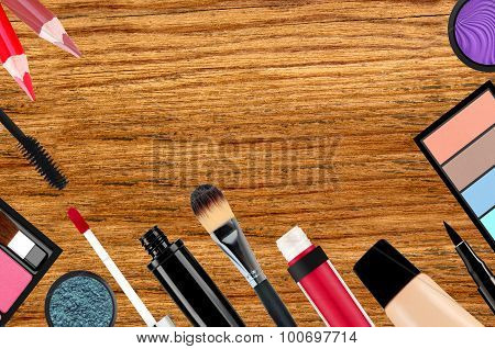 Makeup Brush And Cosmetics Over Wooden Background