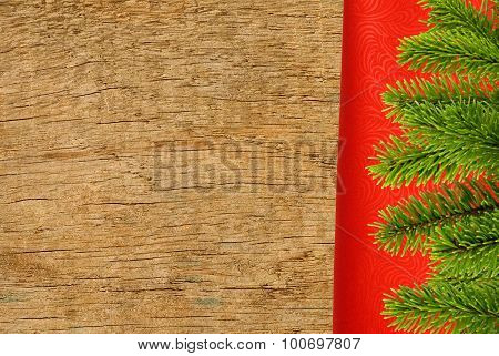 Red Cloth With Fir Tree Branch Over Wooden Texture Close-up