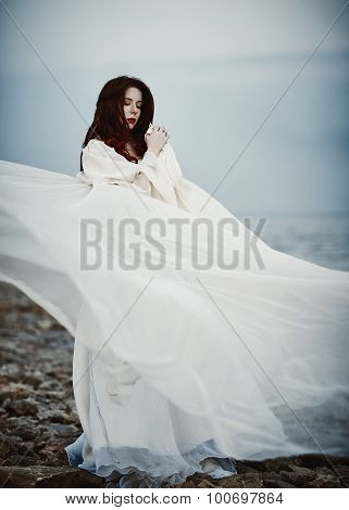 Beautiful Sad Young Woman In White Dress Standing On Sea Beach