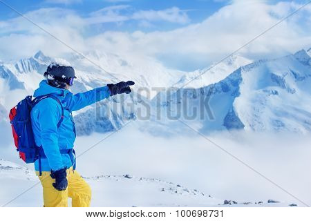 Skier in helmet and goggles with backpack pointing at high snowy mountains