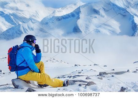 Snowboarder in helmet and goggles, with backpack looking at the mountains