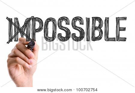 Hand with marker writing the word Impossible