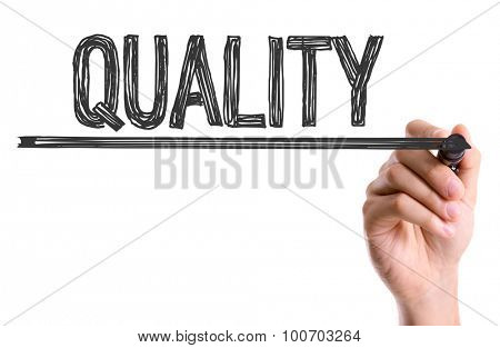 Hand with marker writing the word Quality