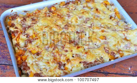 meat casserole with cheese on baking sheet