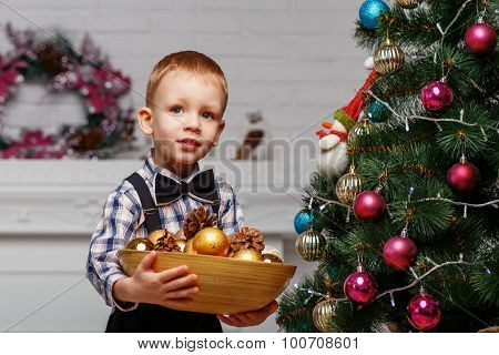 Little Boy Decorates A Christmas Tree In The Interior With Christmas Decorations