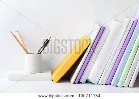 Row Of Books And Stationery In Glass On White Background