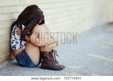 sad girl siitng by brick wall