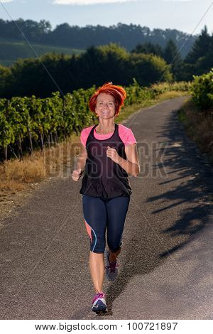 Attractive Redhead Woman Jogging On A Rural Road