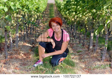 Smiling Athletic Woman Kneeling In A Vineyard