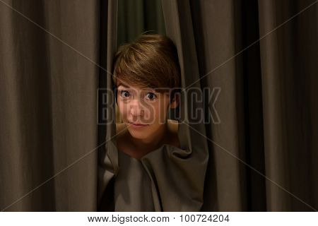 Attractive Woman Peeking Out From Drawn Curtains