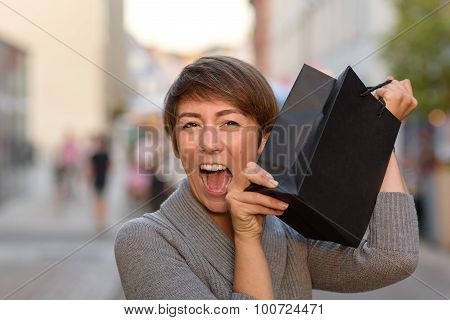 Excited Woman Holding Up A Boutique Bag