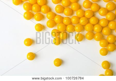 Yellow Pills Are Spilled On The White Surface. Vitamins.