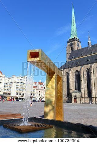 PILSEN CZECH REPUBLIC - SEPTEMBER 1, 2015: Golden fountains against cathedral St. Bartolomew on Republic Square were designed by Ondrej Cisler. European modern architecture.