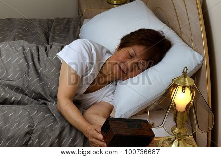 Senior Woman Cannot Sleep At Nighttime While Looking At Clock