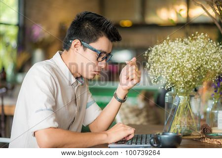 Young Asian Student Man Using Tablet Computer In Cafe