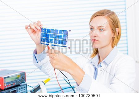 Woman laboratory assistant tests film  solar cells