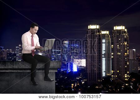 Asian Business Man Working With Laptop On The Building Rooftop
