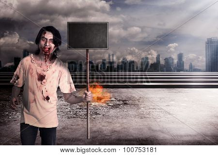 Male Zombie Holding Wooden Board Over City On Fire
