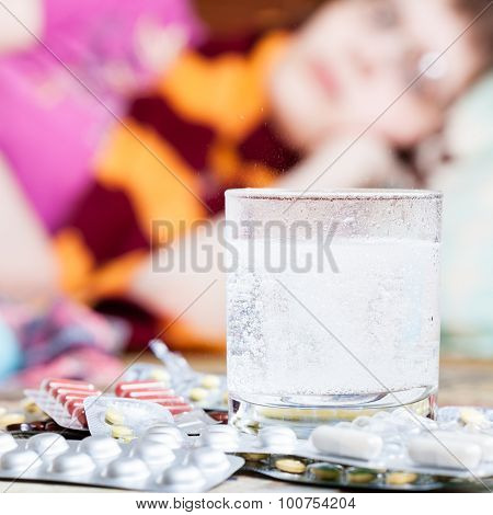 Dissolving Drug In Water And Pills On Table