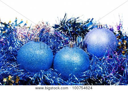Three Blue Christmas Balls And Tinsel Isolated