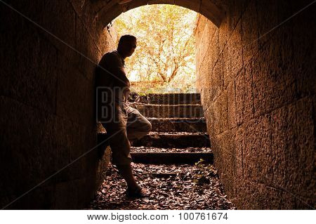 Young Man Stands In Dark Stone Tunnel