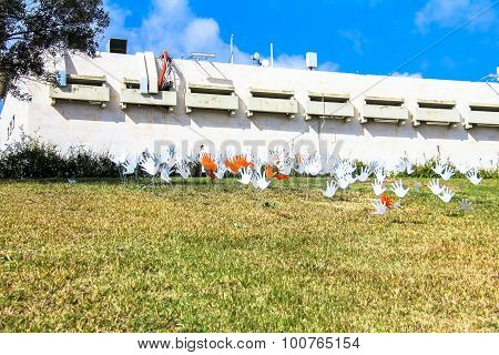 Many waving abstract hands signs or flags installed on a grassy lawn
