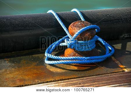 Close-up Of Mooring Bollard With Blue Rope In Marina