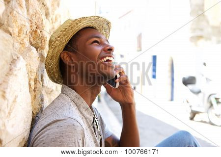 Young Black Man Smiling And Talking On Mobile Phone