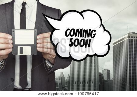 Coming soon text on speech bubble with businessman holding diskette