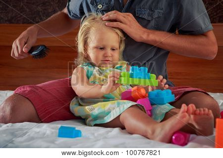 Father Brushes Little Daughter Sitting Near On Sofa