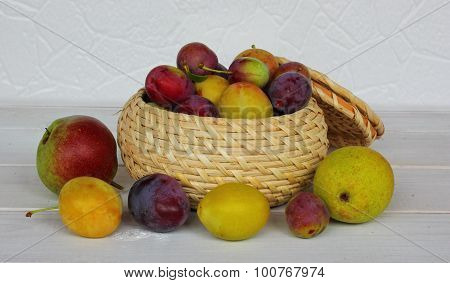 various plums and pears in a wicker pot