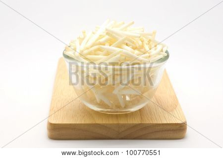 Glass bowl of bean sprouts on wooden board, white background