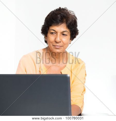 Older people and modern technology concept. Portrait of a 50s Indian mature woman using laptop computer at home. Indoor senior people living lifestyle.