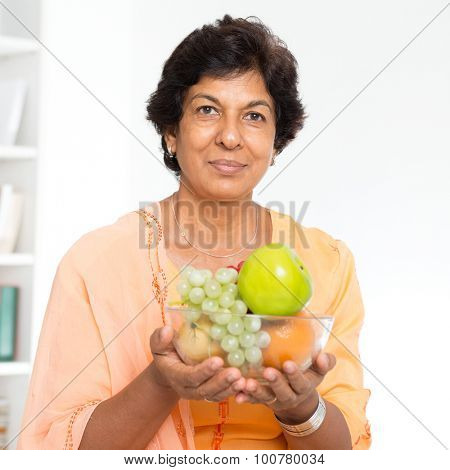Old people healthy eating. Portrait of a 50s Indian mature woman holding fresh fruits at home. Indoor senior people living lifestyle.