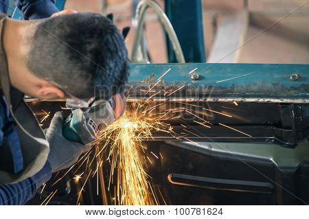 Young Man Mechanical Worker Repairing An Old Vintage Car Body In Messy Garage - Safety At Work