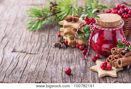 Cranberry sauce in a glass on wooden board