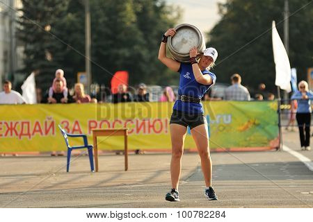 Orel, Russia, September 5, 2015: Slenred Girl In Shorts Carrying Heavy Metal Keg In Competition