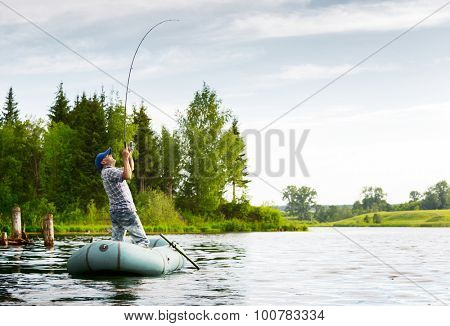 Fisherman with rod in the boat on the calm pond