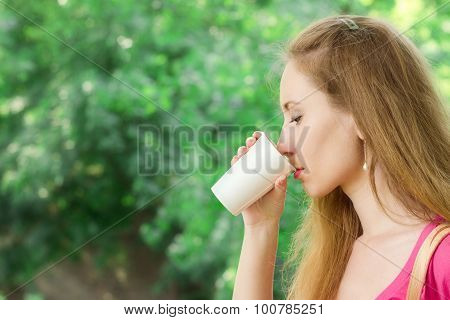 Girl Is Drinking Takeaway Coffee In The Park