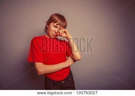 European-looking boy of ten years crying, wiping tears, hurt on