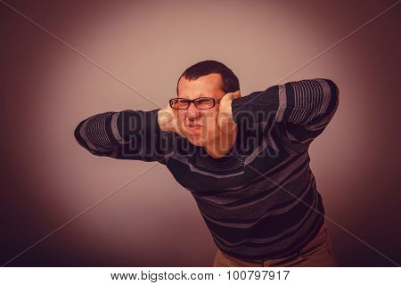 European-looking male covering his ears with his hands brunet on